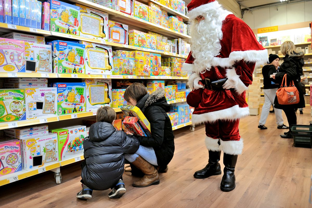 Santa assumes his traditional role of supervising while children pick out their own toys.