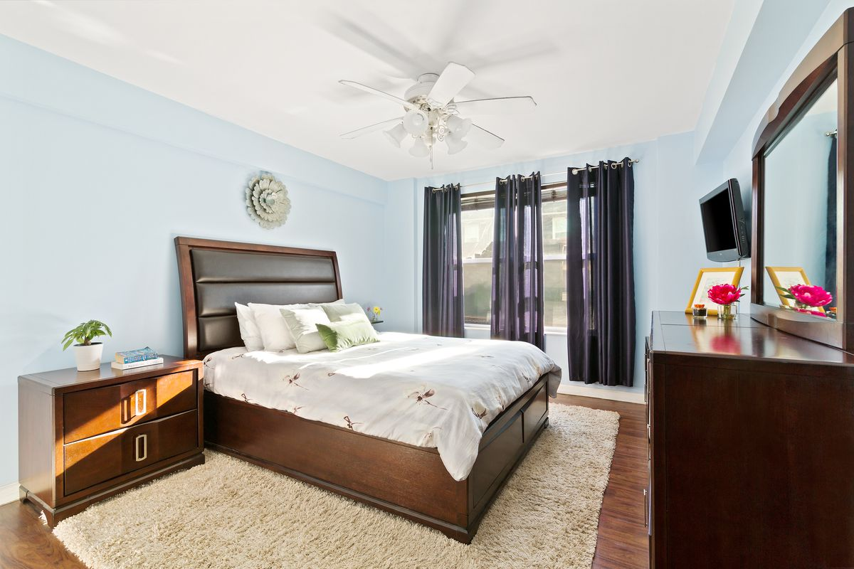 A bedroom with a medium-sized bed, hardwood floors, light blue walls, a light brown rug, and a large window.