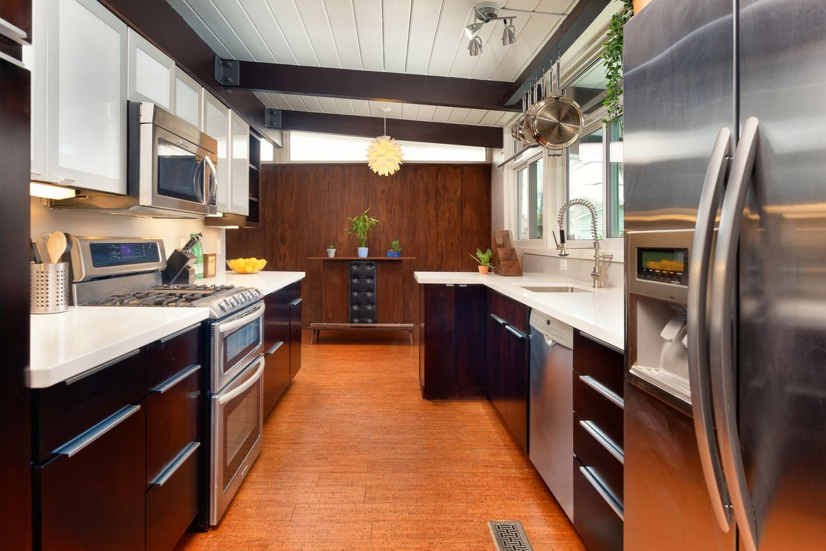 A long and narrow kitchen features dark wood cabinets, white countertops, and stainless steel appliances.