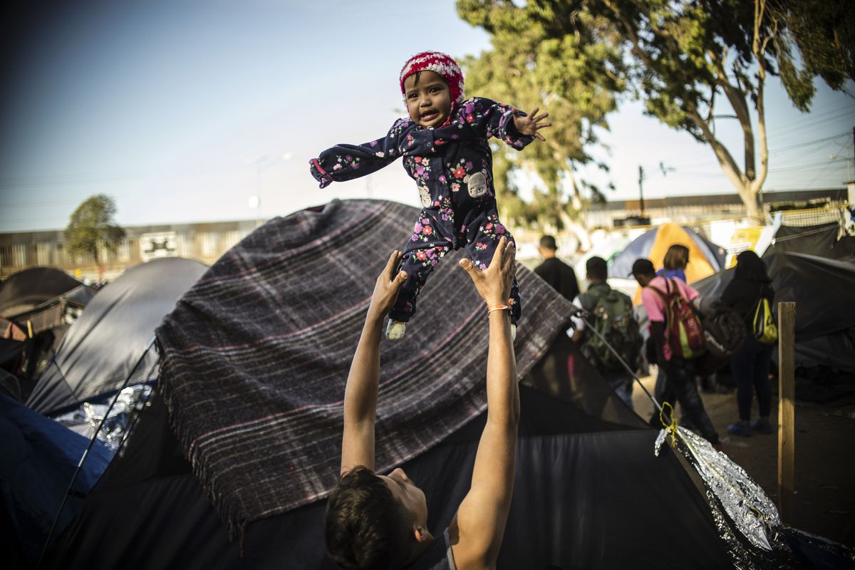 A Central American migrant wanting to reach the United States in hopes of a better life plays with a little child at a shelter in Tijuana, Baja California State, Mexico, near the US-Mexico border fence, on November 23, 2018.