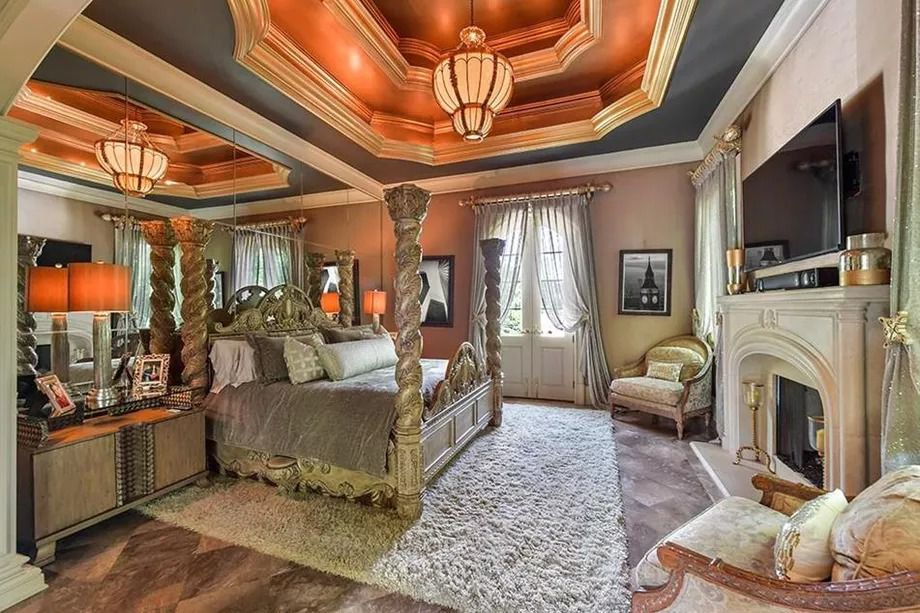 A big master bedroom in Atlanta with a huge fireplace and coffered, gilded ceilings overhead.