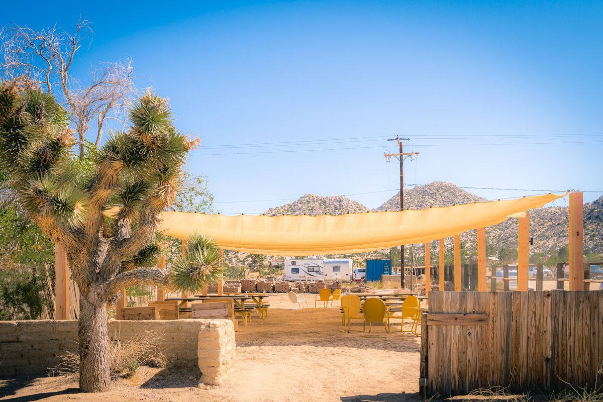 A shaded outdoor sandy patio at a dusty desert restaurant in daylight.