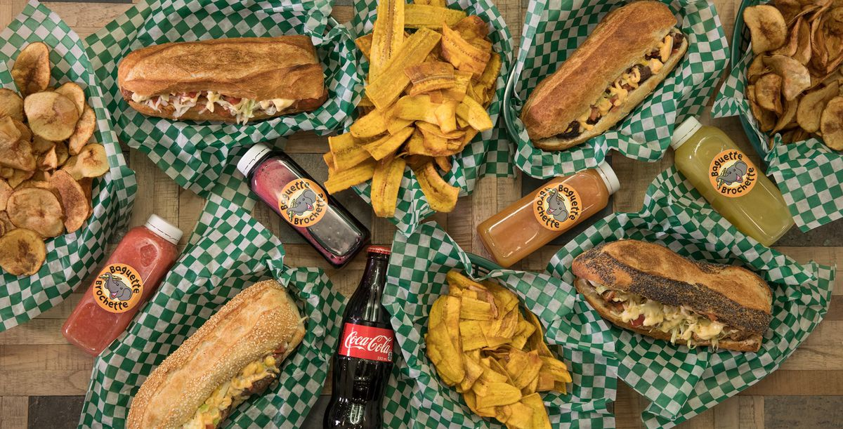 A spread of baguette sandwiches on green checkered paper, with bottles of juice and Coca-Cola in between them.