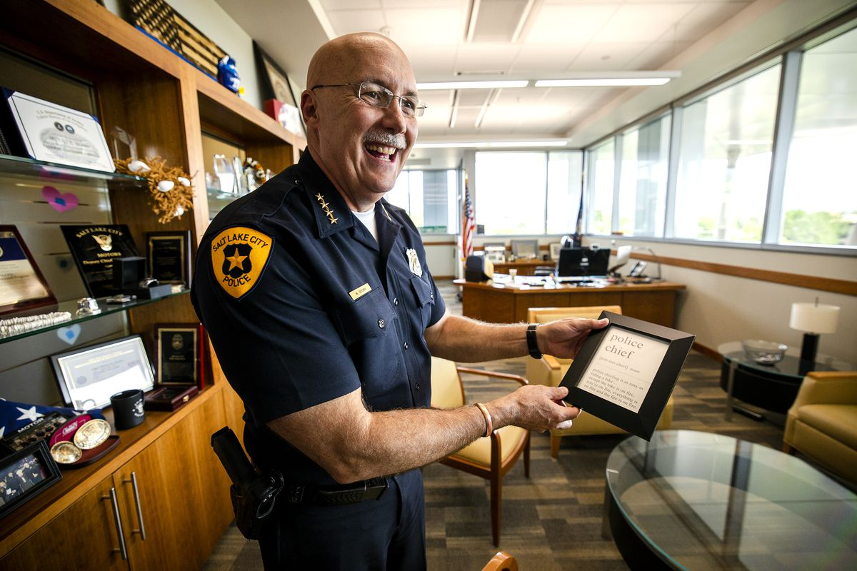 """Salt Lake City Police Chief Mike Brown holds a framed quote that says """"(police chief) [puh-lees cheef] (police chiefing is as easy as riding a bike ... except the bike is on fire, you're on fire, everything is on fire and the fire is on fire.)"""" that he keeps in his office at the Public Safety Building in Salt Lake City following an interview about the morale of the department on Tuesday, July 27, 2021."""