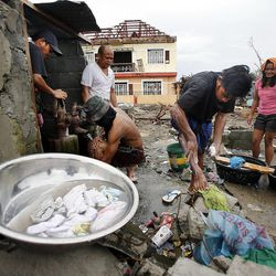 Residents clean up and wash clothing in Tacloban, Friday, Nov. 22, 2013.