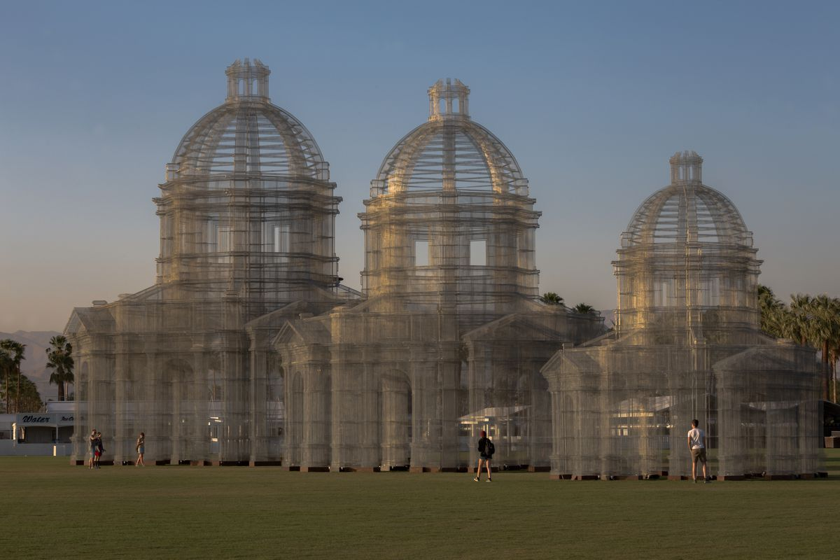 Three transparent domed classical buildings made of wire mesh rise on lawn in park.