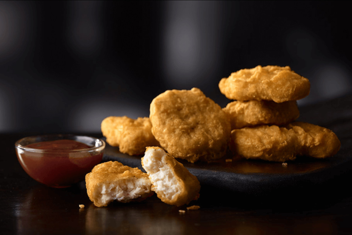 A photo of delicious McDonald's Chicken McNuggets and a bowl of sauce, possibly barbecue