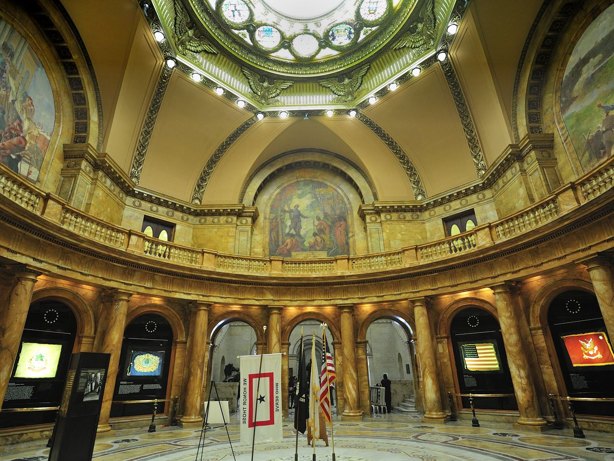 A rotunda with a stained-glass ceiling and flags arrayed around the rotunda.