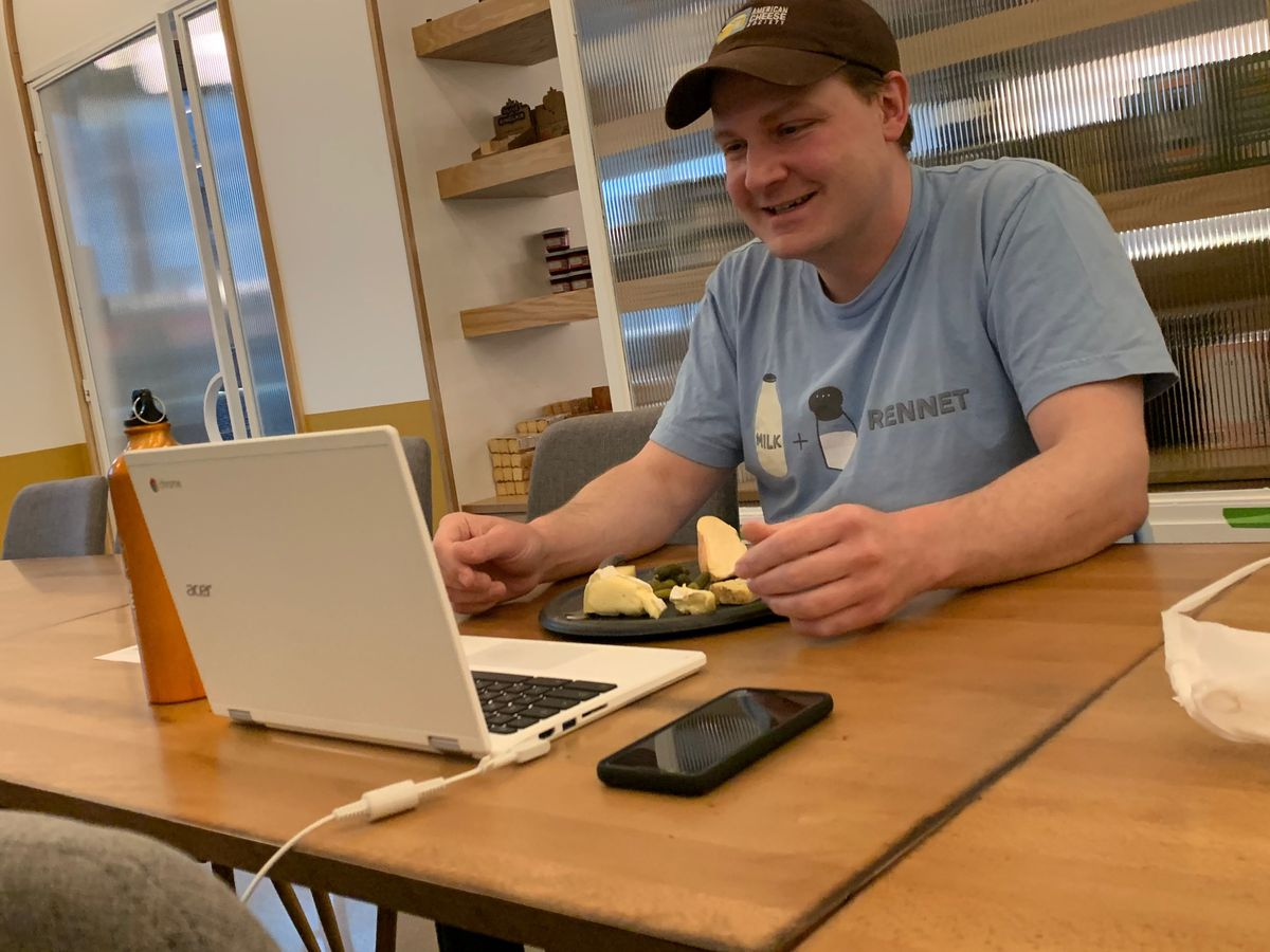 A cheesemonger sits at a computer with a plate of cheese