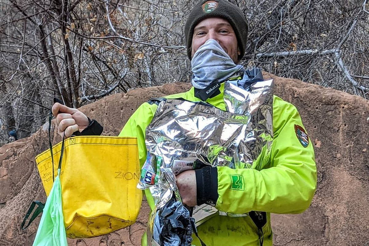 A National Park Service tanger holds bags of trash, including human waste, collected in The Narrows in Zion National Park.