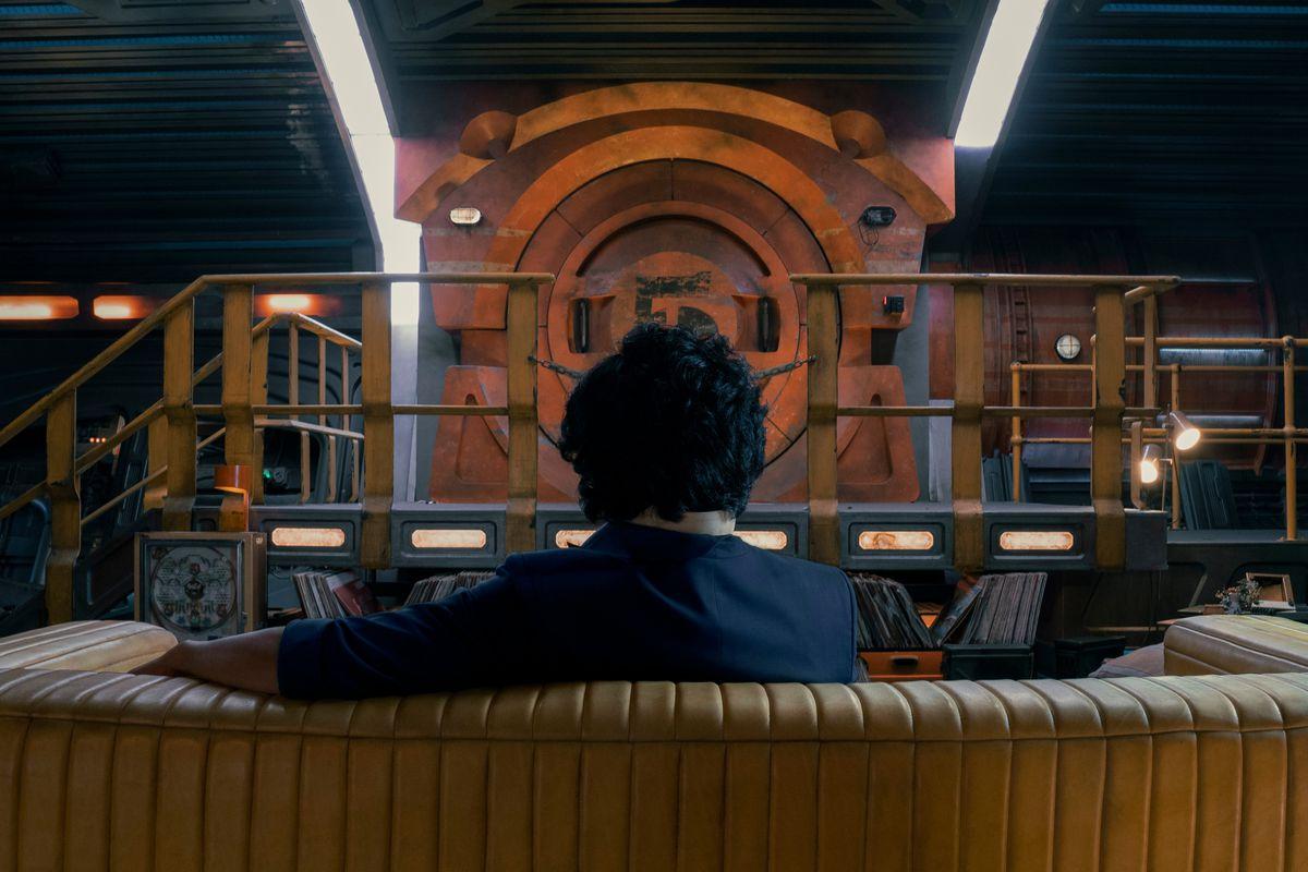 John Cho as Spike Spiegel sitting on a couch in Netflix's Cowboy Bebop