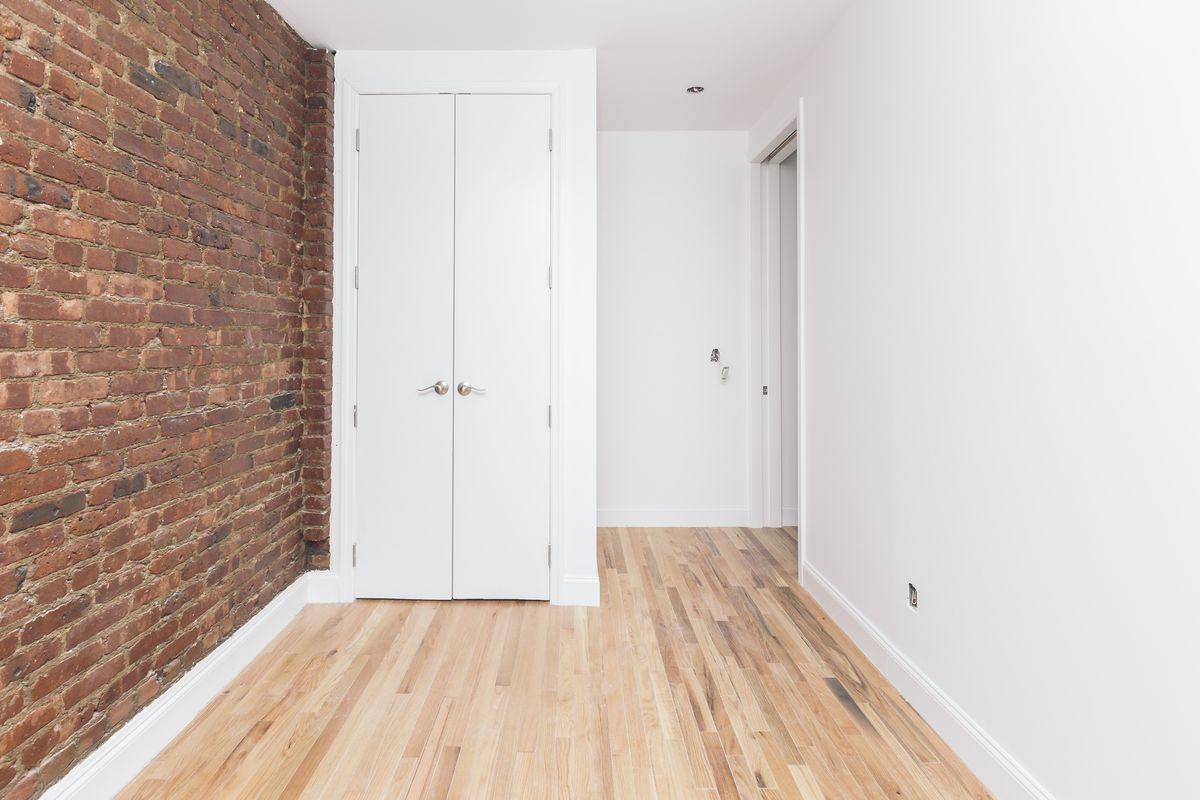 A bedroom with exposed brick, hardwood floors, a small closet, and white walls.