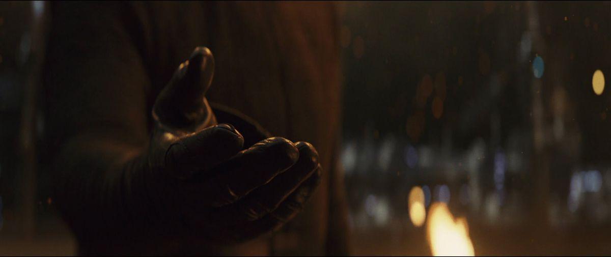 Kylo Ren's (Adam Driver) black-gloved hand reaches for Rey's in Star Wars: The Last Jedi.