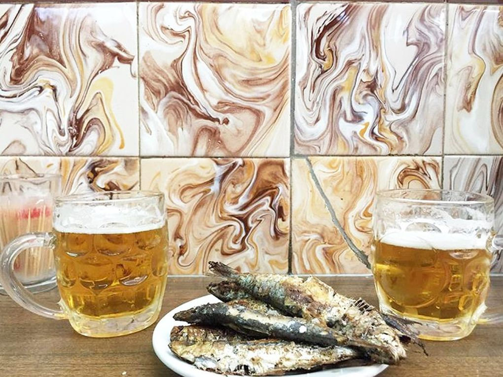 Two beers on either side of a plate of sardines in front of a loud, textured wall.
