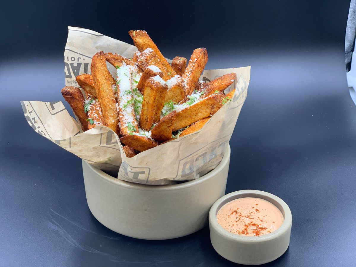 Chile, lime, and cotija-dusted fries sit in brown paper inside a white bowl, with a smaller white bowl of a reddish white dipping sauce sitting next to it