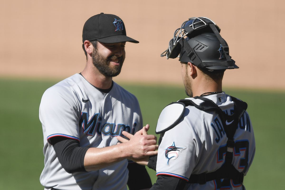 Dylan Floro #36 of the Miami Marlins, left, is congratulated by Alex Jackson #23 after the Marlins beat the San Diego Padres 7-0 in a baseball game at Petco Park