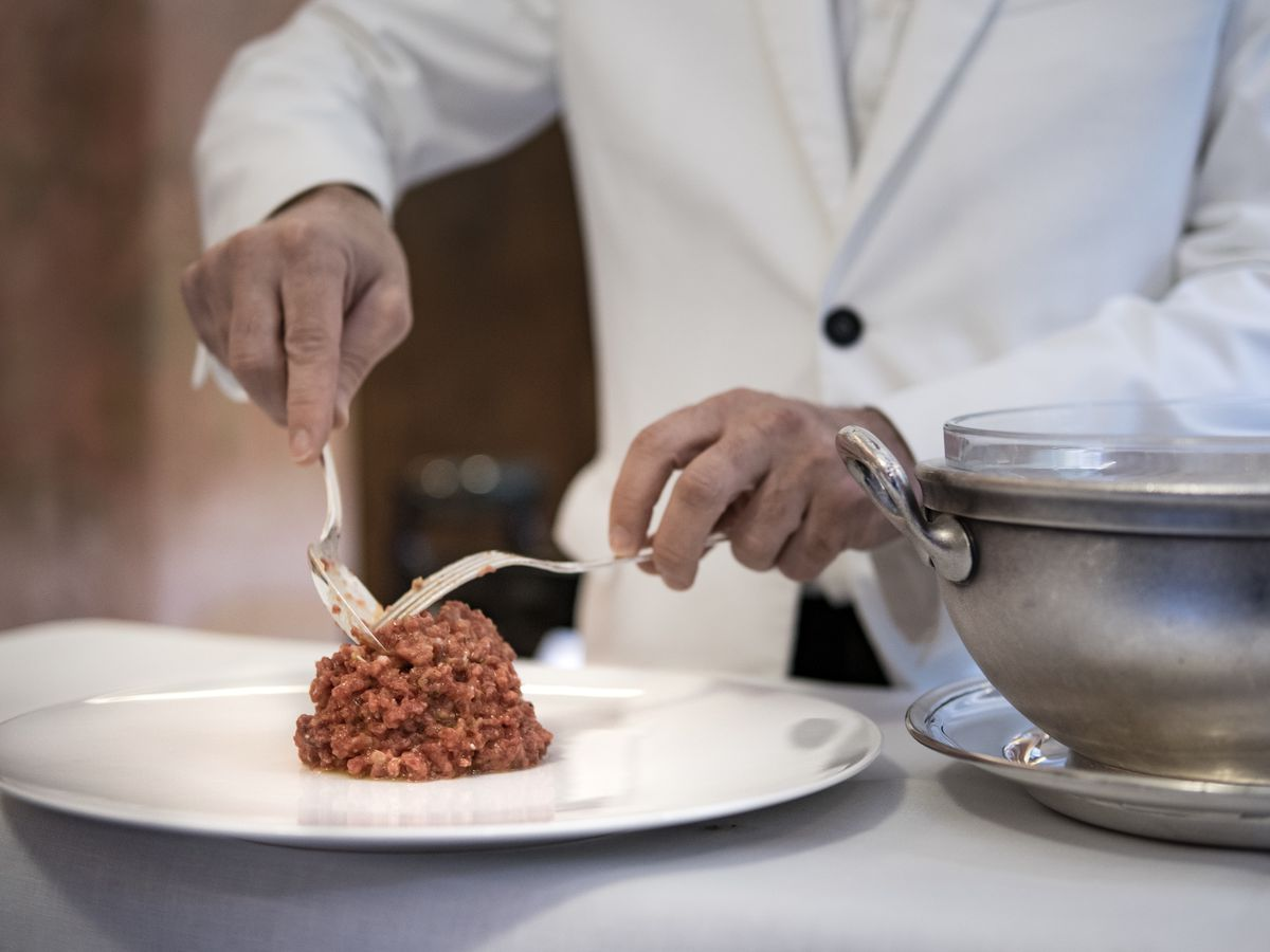 A chef sculpts a mound of steak tartare with two forks