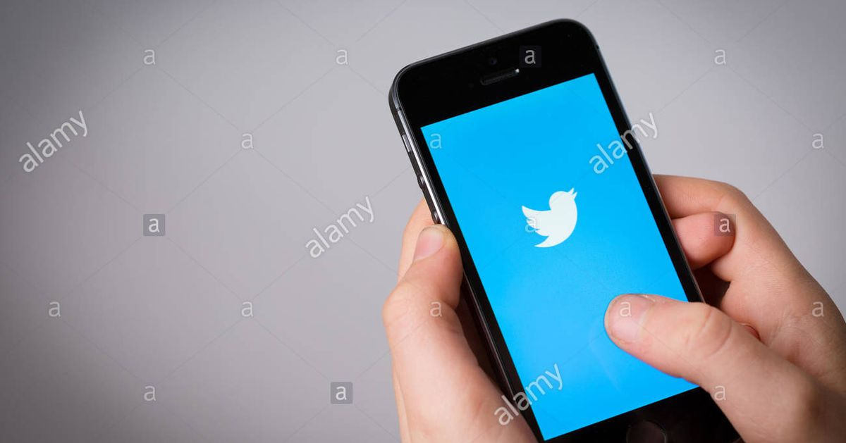 A_teenage_boy_using_twitter_on_a_mobile_phone_hn1et4