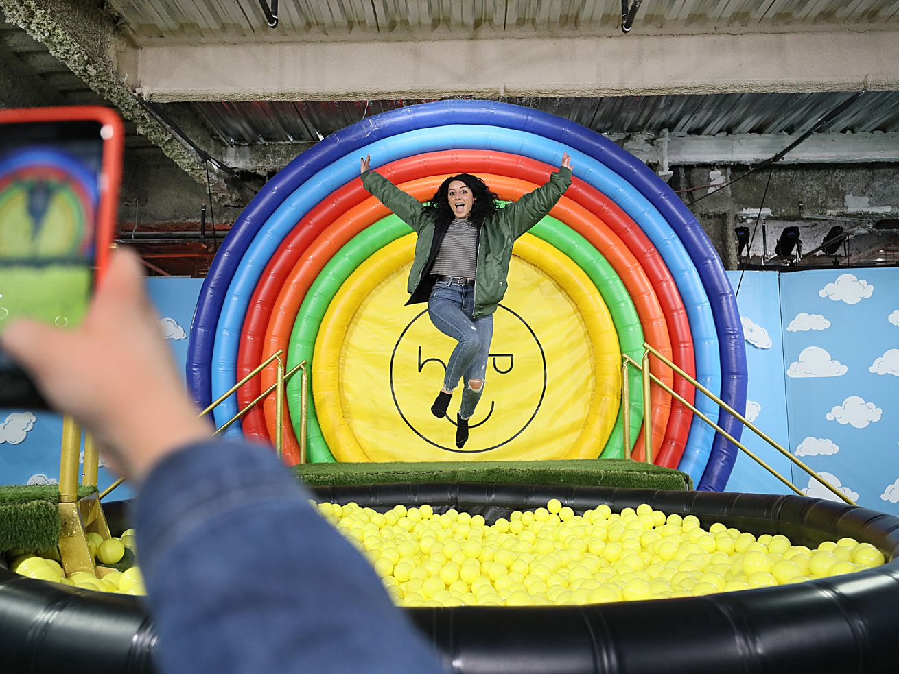 A young woman jumps into a ball pit in front of a rainbow bulls-eye design.
