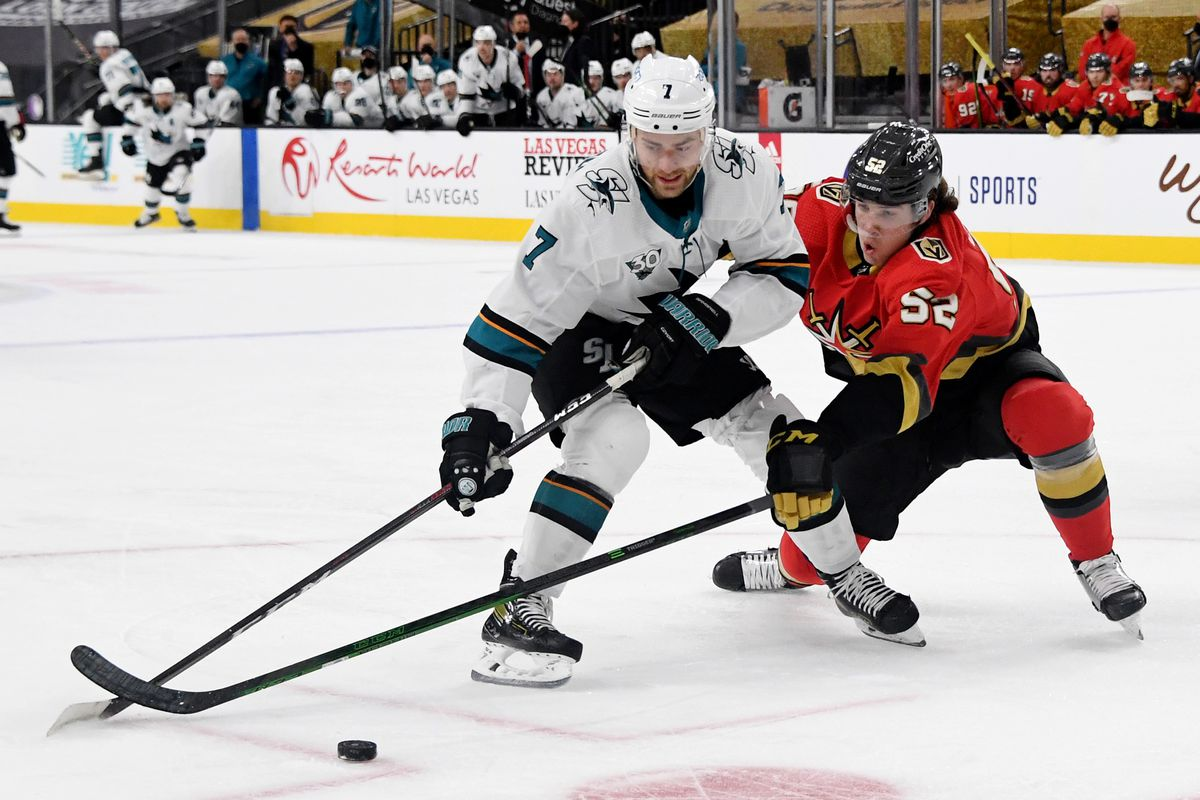 Dylan Gambrell #7 of the San Jose Sharks and Dylan Coghlan #52 of the Vegas Golden Knights fight for the puck in the first period of their game at T-Mobile Arena on March 15, 2021 in Las Vegas, Nevada. The Golden Knights defeated the Sharks 2-1.
