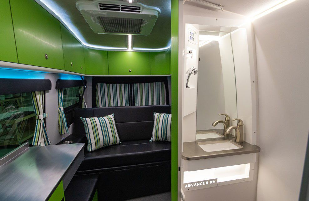 A view into the camper's all-white bathroom with a small sink and LED lighting.