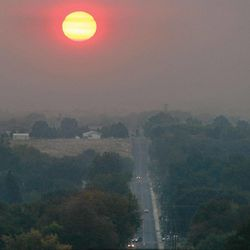 The glow from Thursday morning's sunrise is heavily filtered through layers of hazy smoke from regional wildfires that settled overnight around the Tri-Cities, Thursday, Sept. 20, 2012 in Kennewick, Wash.. The smoky conditions have prompted area school districts to cancel outdoor sports events and move physical education classes indoors.