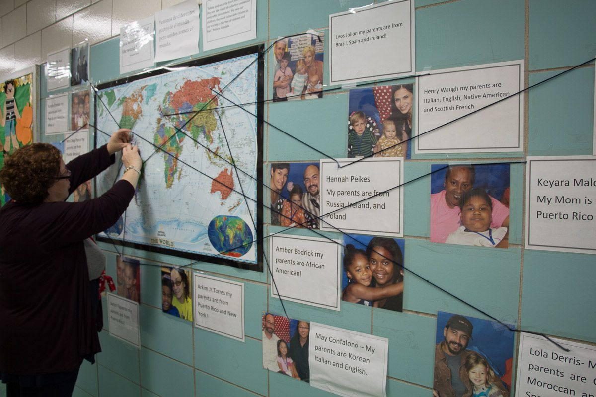 P.S. 15 teacher Giselle Ruiz stands in front of a bulletin board that shows the ethnicities of her students' families.