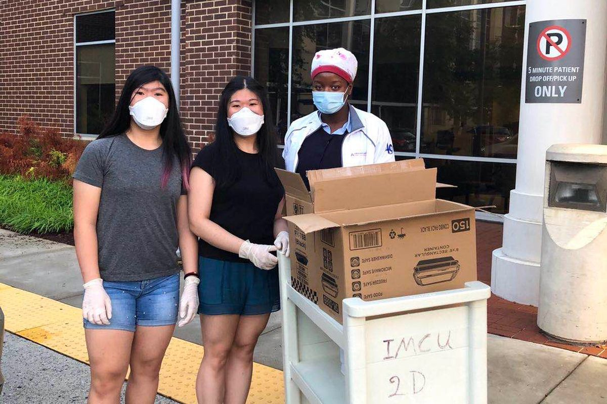 Catherine Shi and Grace Shi deliver a cart full of meals to a hospital worker