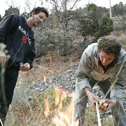 Tyson Lloyd, left, and Eric Richardson, right, build a fire to cook their dinner. They have been living in a tent since May to save money and avoid debt.