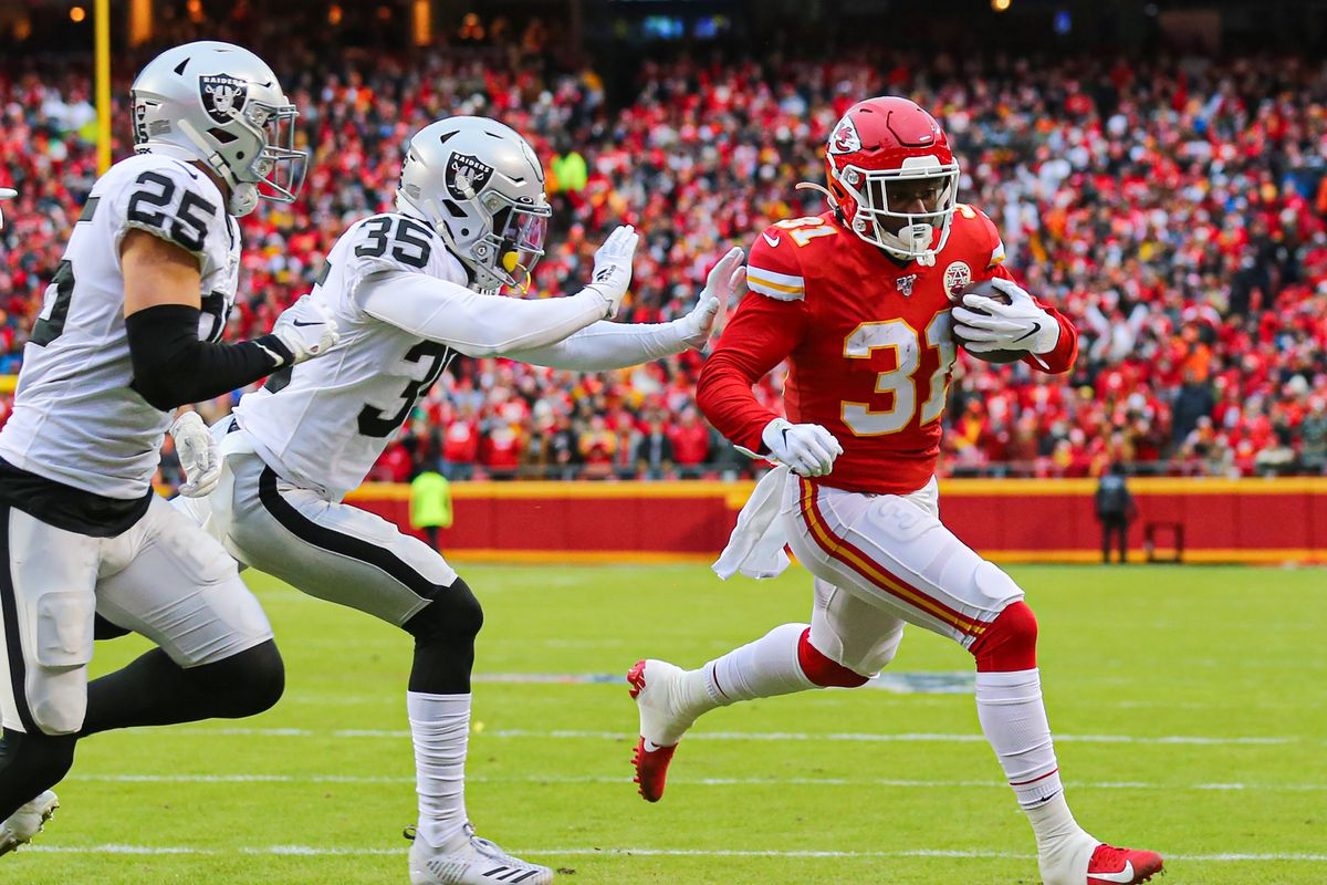 Kansas City Chiefs running back Darrel Williams runs for a touchdown against Oakland Raiders free safety Erik Harris and free safety Curtis Riley during the first half at Arrowhead Stadium.