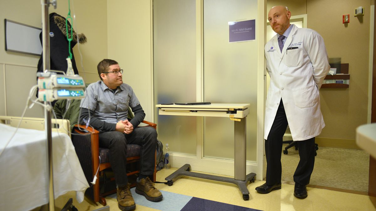 Dr. Ryan Merkow (right), a surgical oncologist, talks with his patient Sean O'Reilly, who is receiving chemotherapy with a specialized hepatic artery infusion pump at the Robert H. Lurie Comprehensive Cancer Center of Northwestern Memorial Hospital.