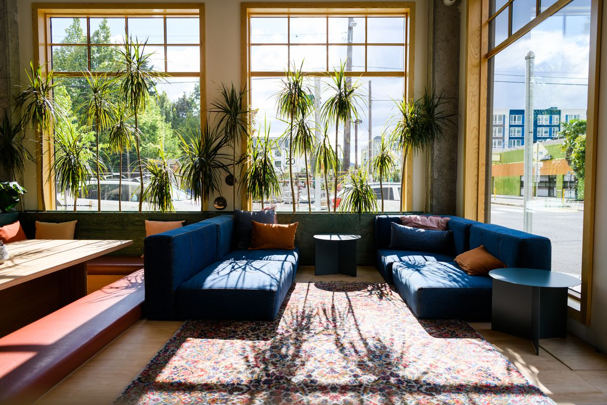 Two low-to-the-ground denim couches sit on a rug in the windows of Lolo Pass