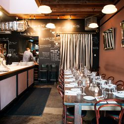 """Naomi Pomeroy's small but bustling Beast, with nothing but a butcher's block and two communal tables, best represents Portland's """"intimate supperclub"""" aesthetic: a """"chalkboard""""-style black wall features irreverent scrawls, lights dim and tables glow with"""