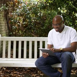A man uses a tablet to look up his family tree.
