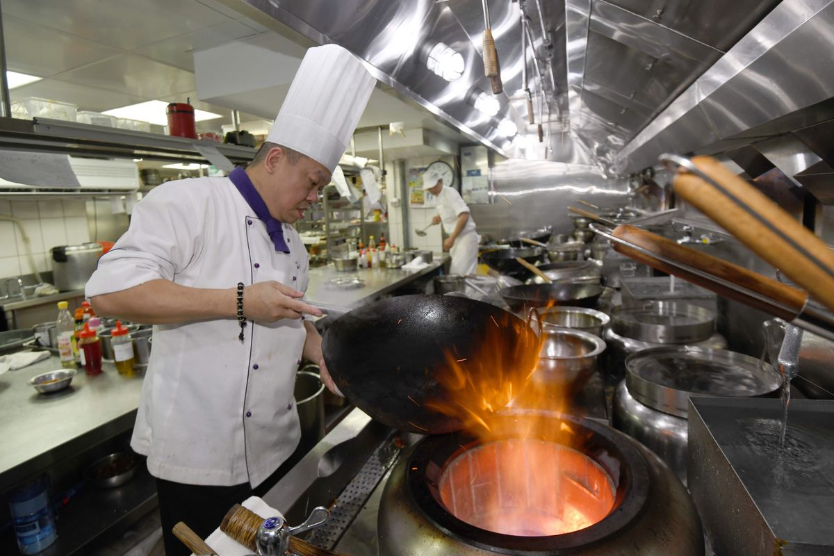 Ken Chan, executive chef of Le Palais restaurant in Taipei, Taiwan, stands over a wok with huge flames.
