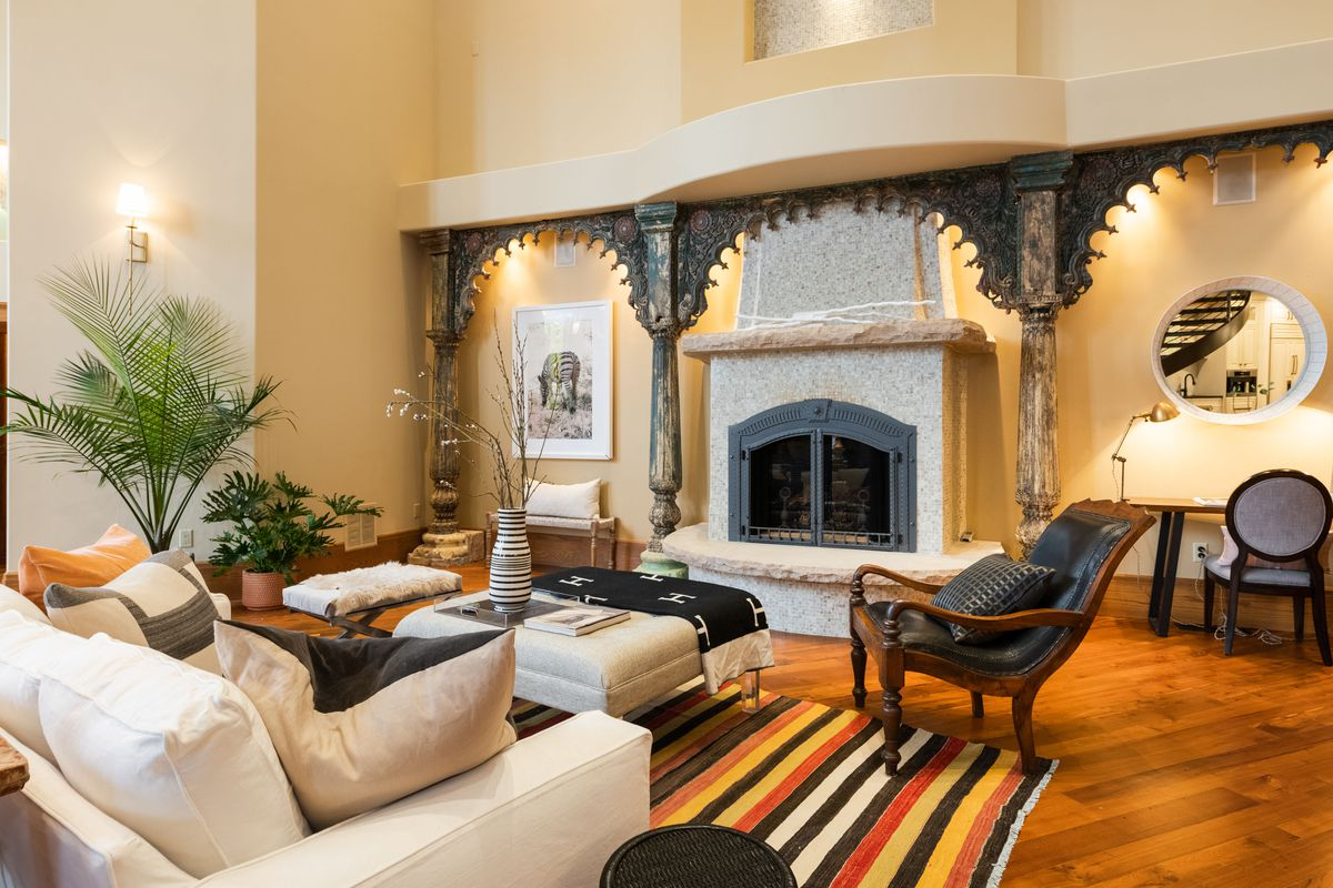 A white seating area with chairs is centered around a fireplace.