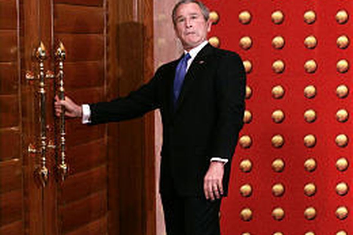 President Bush jokingly makes a face as he tries to open a locked door while leaving a press conference in Beijing Sunday. He made better progress on economic issues.