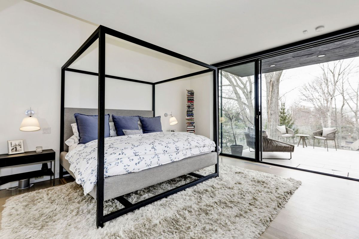 A large bed sits on a shag gray rug with views out to a patio.