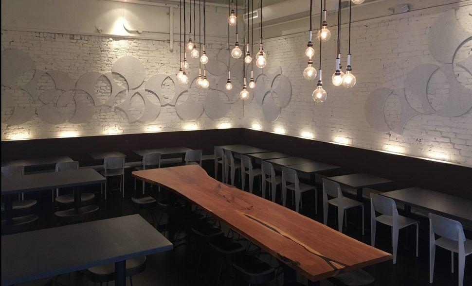 An empty dining room with white painted brick walls decorated with circular white disks. Different lengths of lights hang from the ceiling over a long natural wood table.