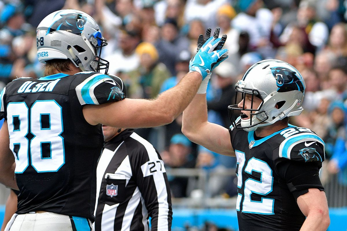 Christian McCaffrey celebrates with teammate Greg Olsen of the Carolina Panthers after a touchdown against the Green Bay Packers in the first quarter during their game at Bank of America Stadium on December 17, 2017 in Charlotte, North Carolina.