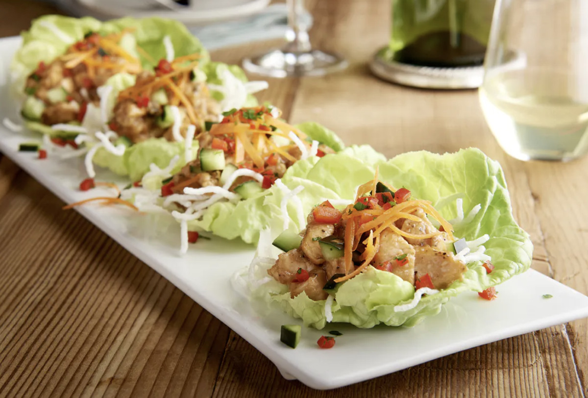 Lettuce wraps sit on a long, rectangular white plate and are accompanied by a glass of white wine.
