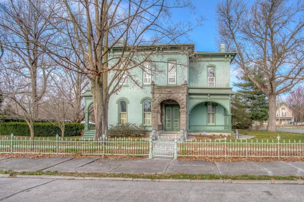 Exterior shot of an aqua-green stone and brick Italianate two-story home with arched windows and covered patios.