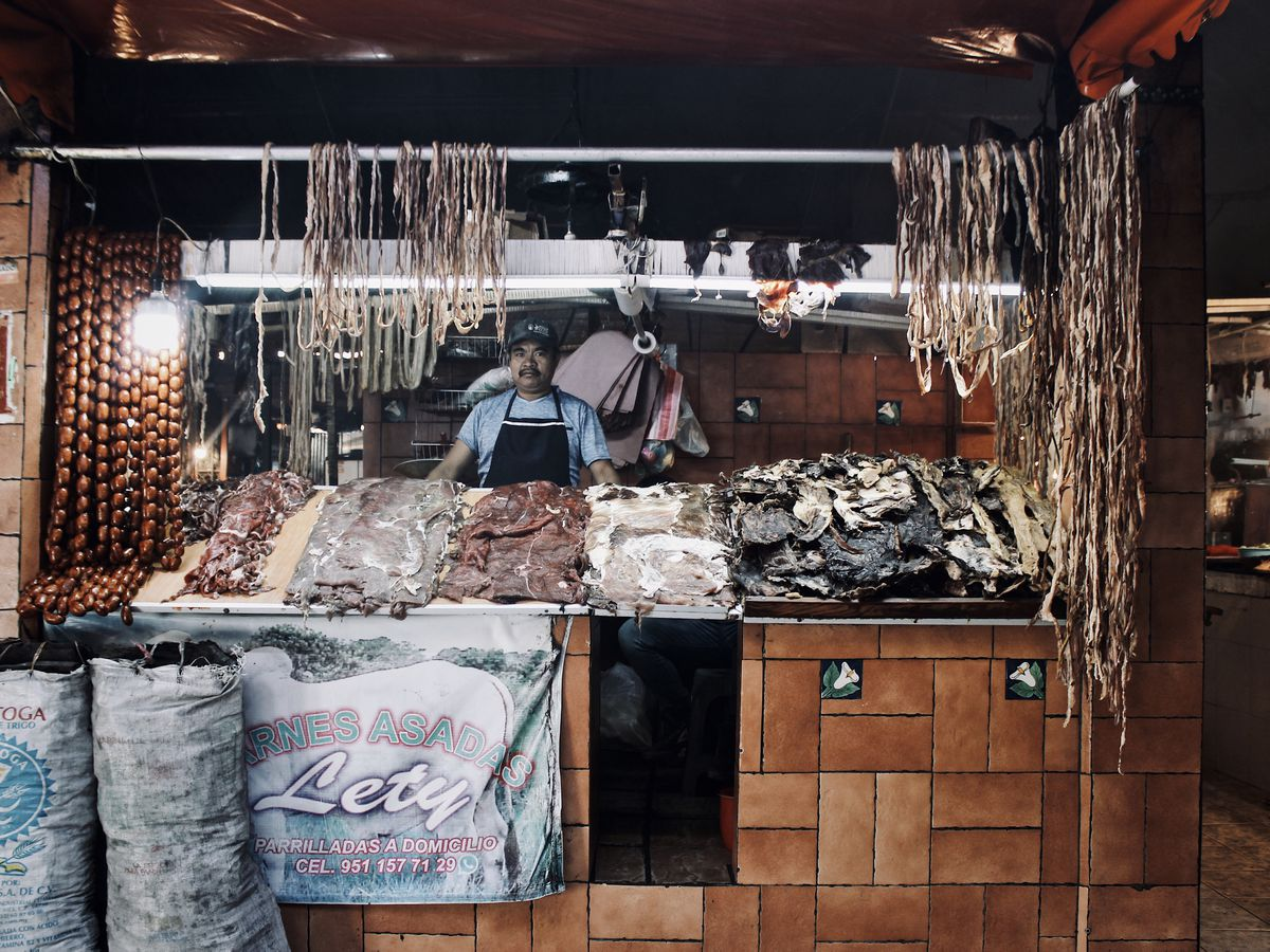 a man stands behind a stall covered with dried meat products.