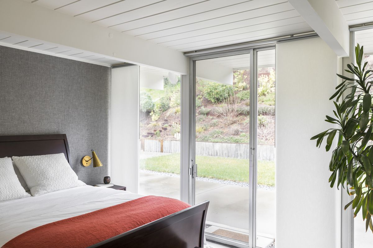 The master bedroom has a fabric wallcovering behind the bed.