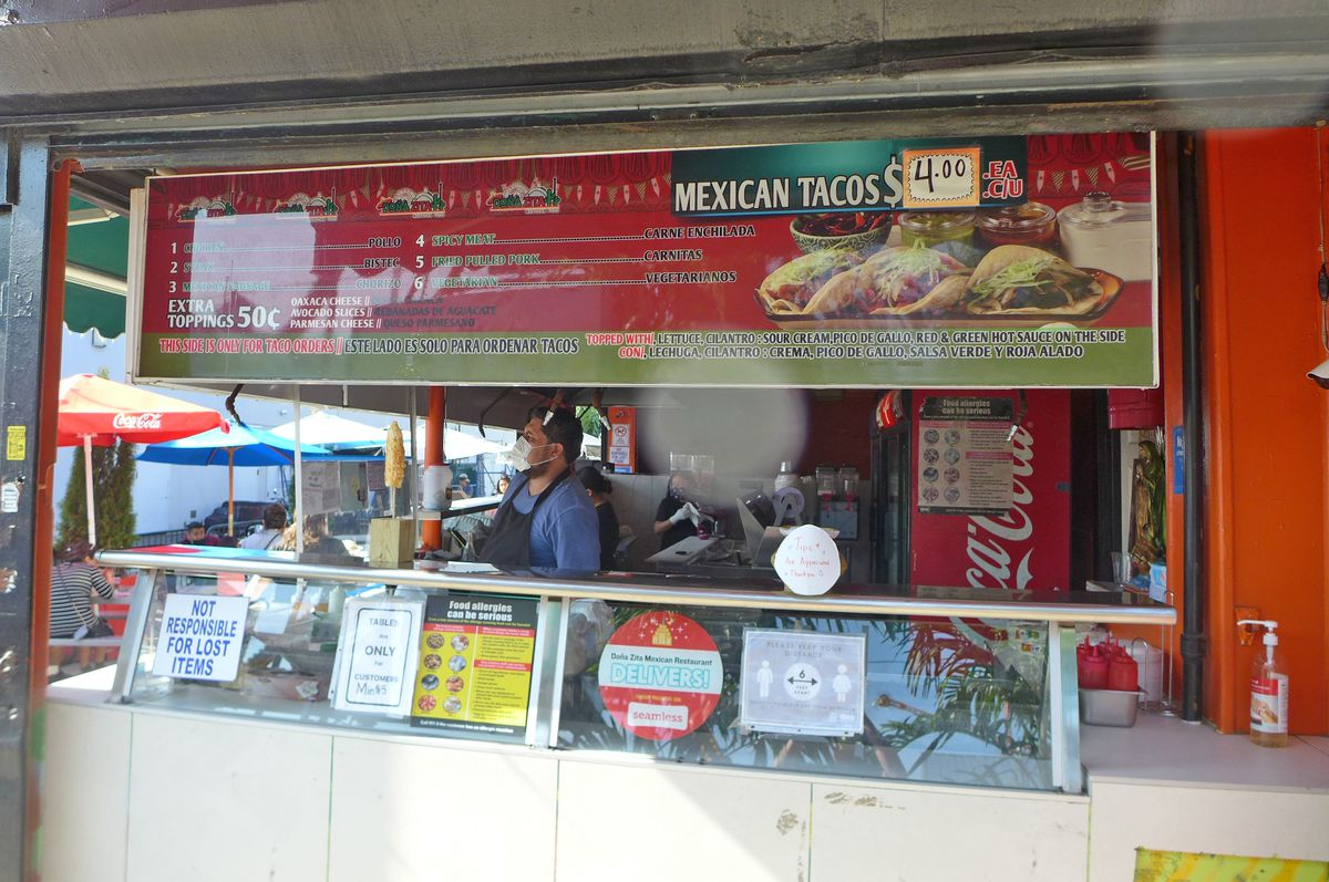 A counter with a menu on a red surface above the window.