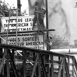 Workers set up a sign, warning pedestrians they are leaving the American sector of Berlin, Germany, at the Wiener Strasse (Vienna Street) in the district of Kreuzberg in West Berlin August 13, 1961. Background right is the Berlin wall that divides East and West Berlin.