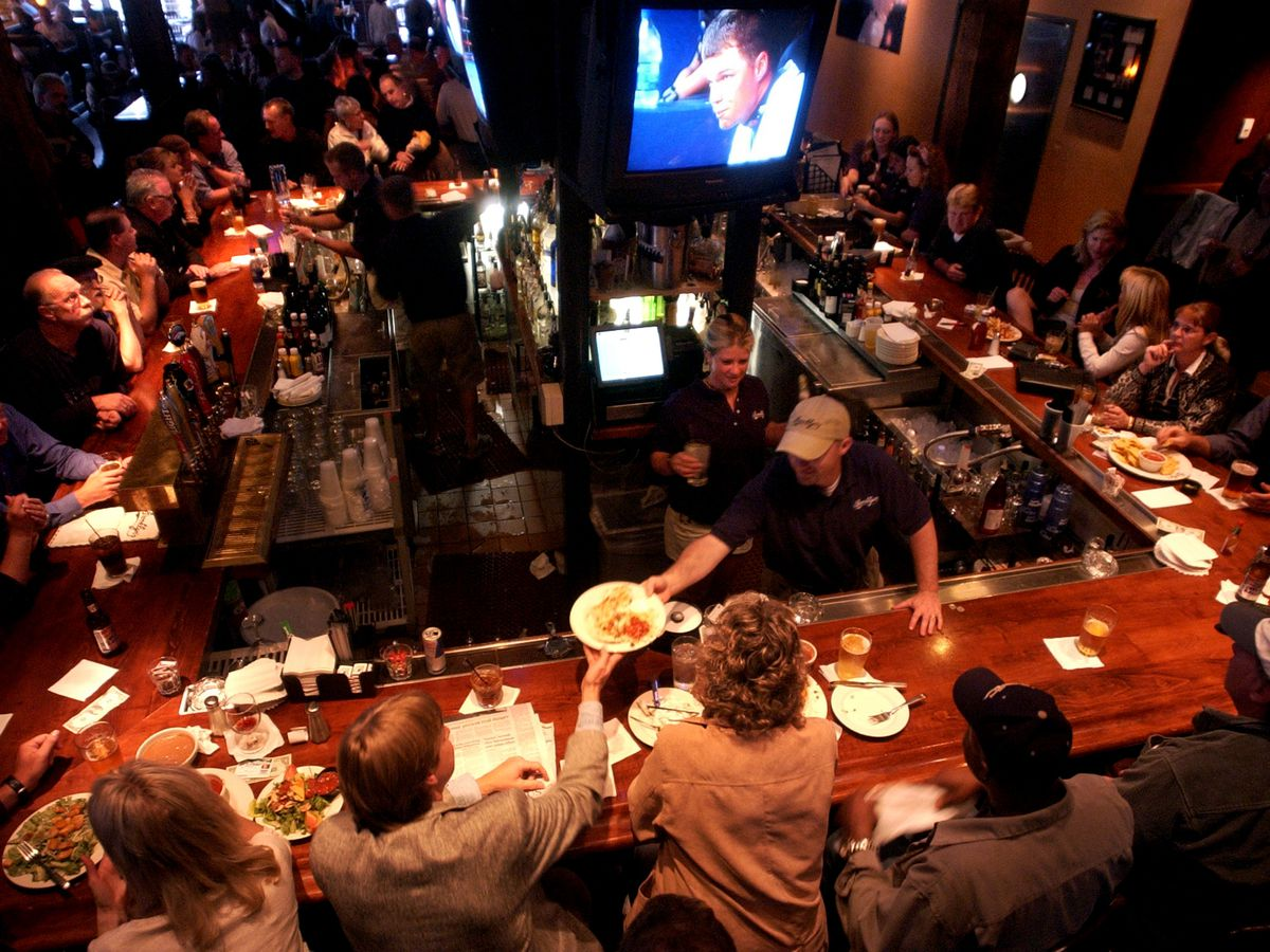 A photo of a bar filled with patrons and bartenders serving them at Brooklyn's at the Pepsi Center