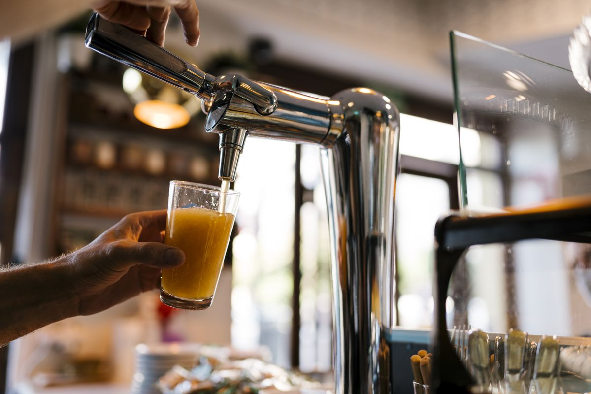 A glass of beer being filled at a tap.