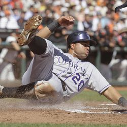 Colorado Rockies' Wilin Rosario slides safely into home plate to score the Rockies first run during the second inning of a baseball game against the San Francisco Giants in San Francisco, Thursday, Sept. 20, 2012.