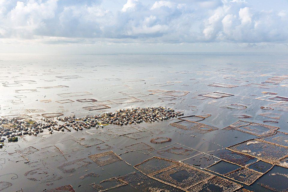 An aerial view of a fish farm with a floating village in the center.